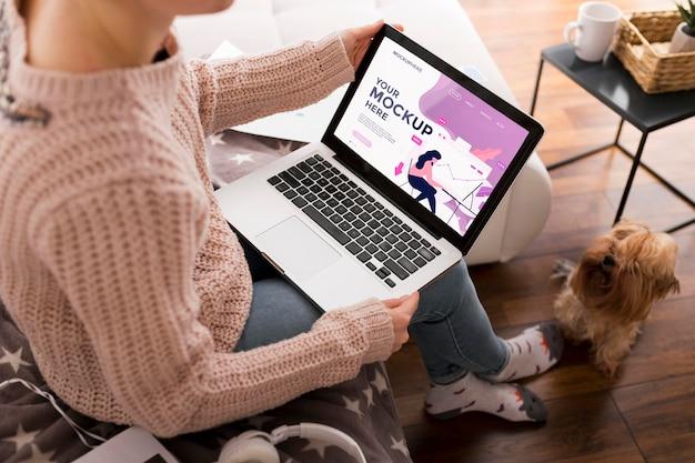 Mujer en casa con maqueta de laptop