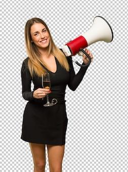 Mujer con champagne celebrando año nuevo 2019 sosteniendo un megáfono
