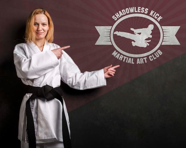 Mujer con cinturón negro de karate y maqueta de artes marciales