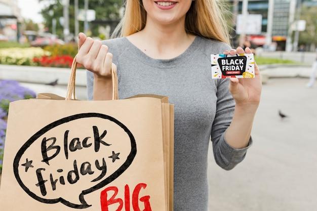Mujer en ciudad con bolsas de black friday