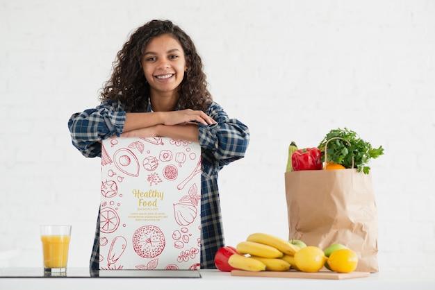 Mujer en cocina con frutas y verduras saludables