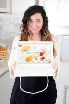 Mujer en cocina presentando mockup de portátil