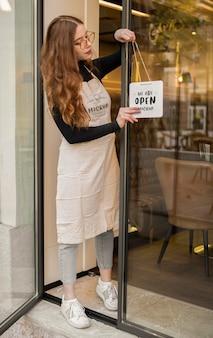 Mujer colgando un cartel de maqueta estamos abiertos