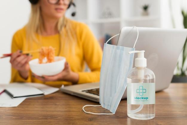 Mujer comiendo en el escritorio con maqueta de desinfectante