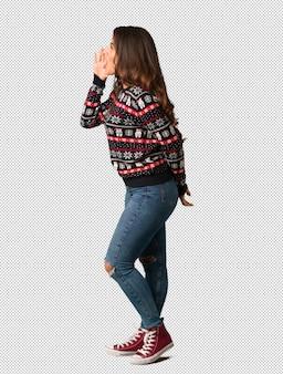 Mujer de cuerpo completo con un jersey de navidad susurrando chisme bajo tono