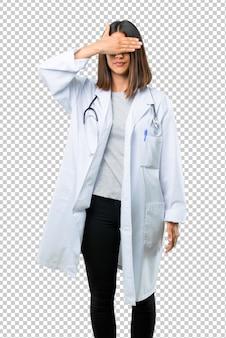 Mujer del doctor con los ojos de la cubierta del estetoscopio por las manos. no quiero ver algo