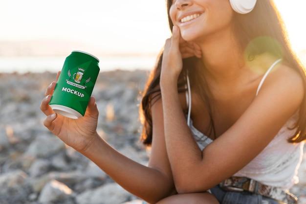 Mujer escuchando música en auriculares con lata de refresco