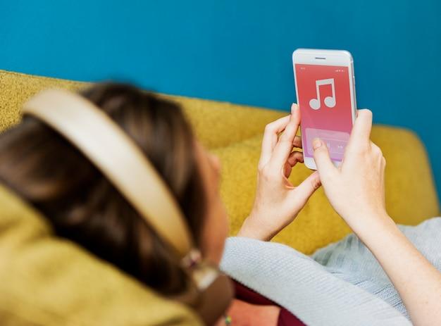 Mujer escuchando música en el sofá