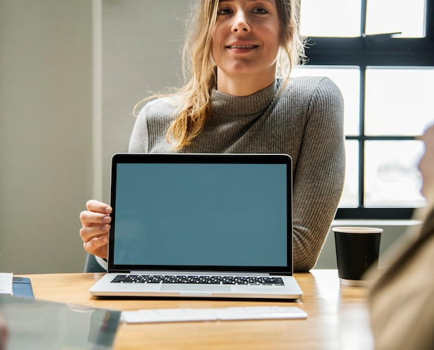 Mujer feliz con una pantalla en blanco de la computadora portátil