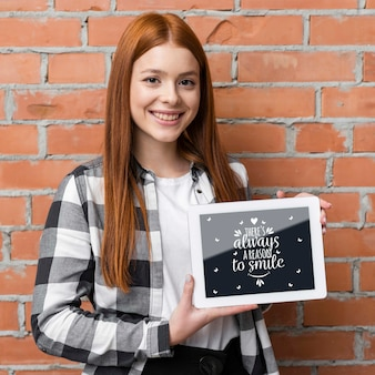 Mujer feliz que sostiene la maqueta de la tableta
