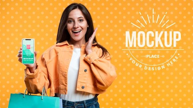 Mujer feliz sosteniendo bolsas de la compra y una maqueta de teléfono