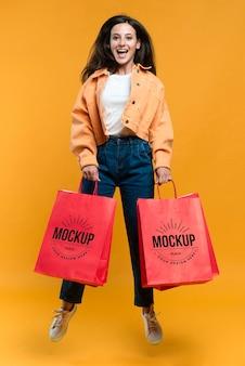 Mujer feliz sosteniendo bolsas de la compra.