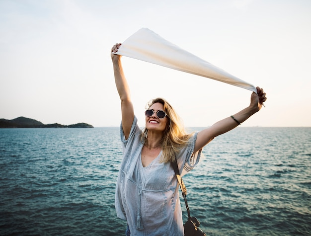 Mujer frente al mar con bandera