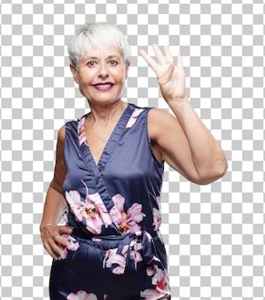 Mujer fresca mayor que sonríe y que parece satisfecha y feliz, contando el número cuatro con los dedos.