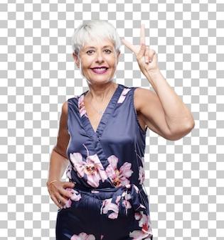 Mujer fresca mayor que sonríe y que parece satisfecha y feliz, contando el número dos con los dedos.