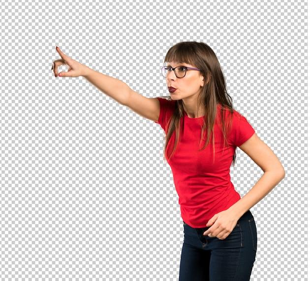 Mujer con gafas apuntando lejos