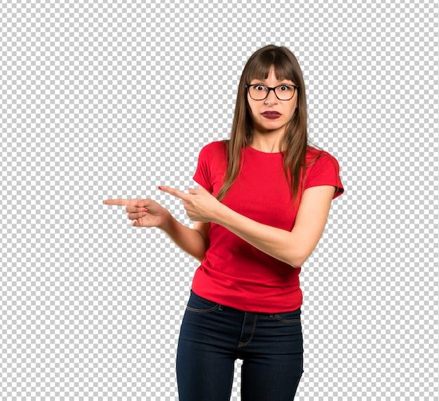Mujer con gafas asustada y apuntando hacia el lado.