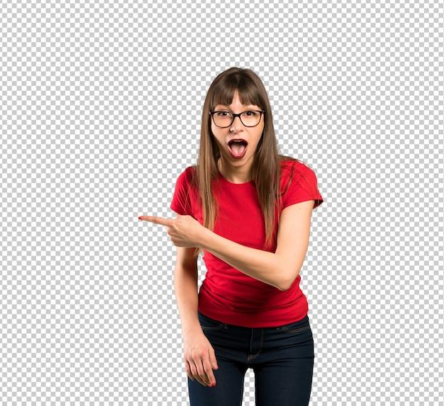 Mujer con gafas sorprendida y apuntando al costado.
