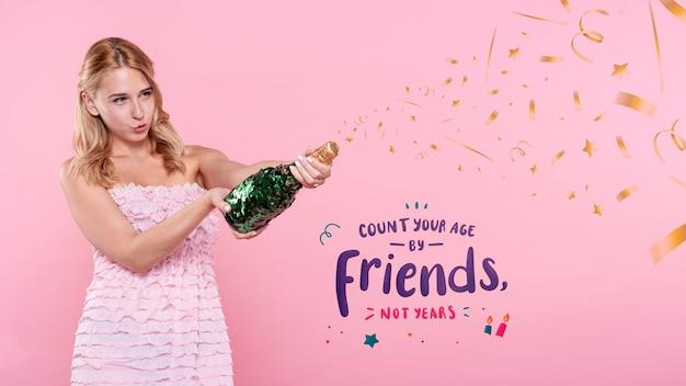 Mujer haciendo estallar la botella de champán en la fiesta