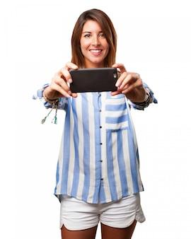 Mujer joven alegre haciéndose una foto
