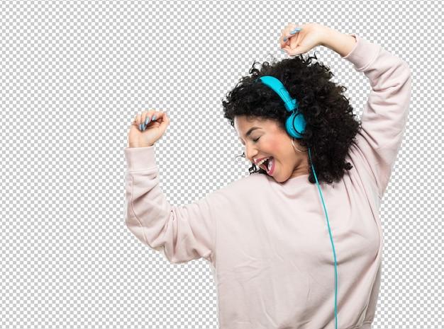Mujer joven bailando y escuchando música.