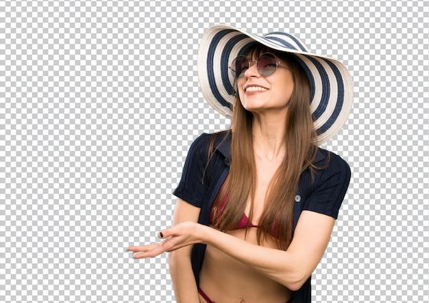 Mujer joven en bikini extendiendo las manos hacia un lado para invitar a venir.