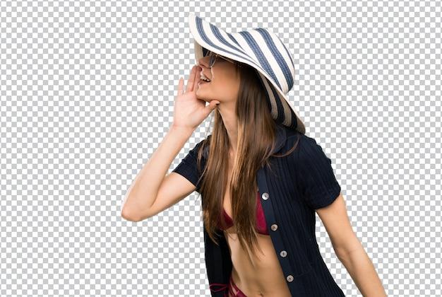 Mujer joven en bikini gritando con la boca abierta