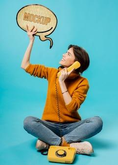 Mujer joven con burbuja de chat y teléfono antiguo