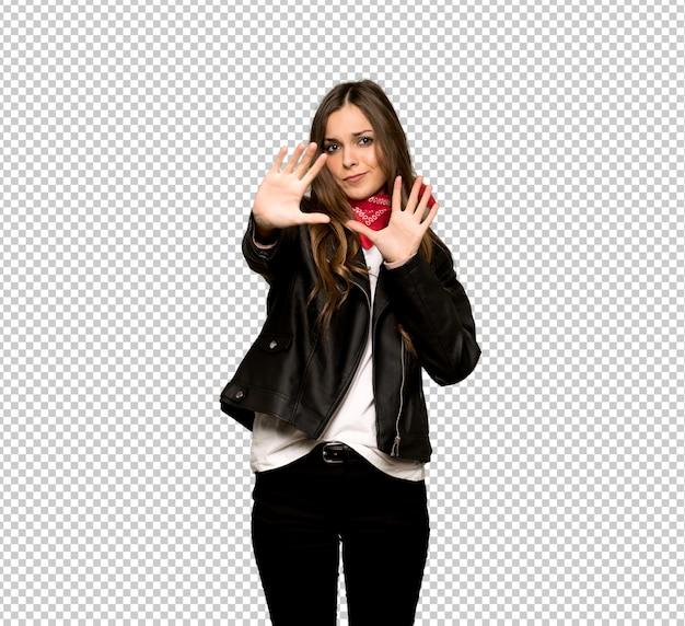 Una mujer joven con chaqueta de cuero está un poco nerviosa y asustada estirando las manos hacia el frente.