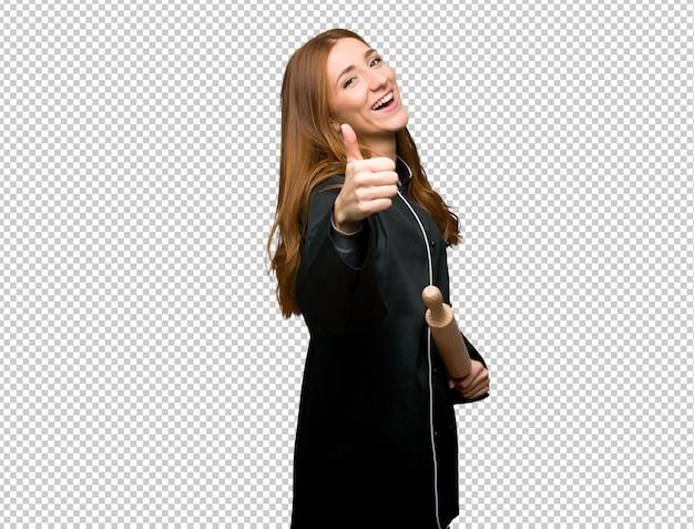 Mujer joven chef pelirroja haciendo un gesto de aprobación porque algo bueno ha sucedido