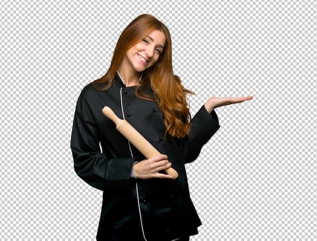 Mujer joven del cocinero del pelirrojo que presenta una idea mientras que mira sonriente hacia