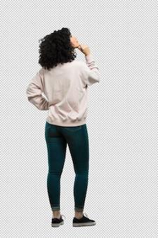 Mujer joven de cuerpo completo hacia atrás y mirando hacia arriba.