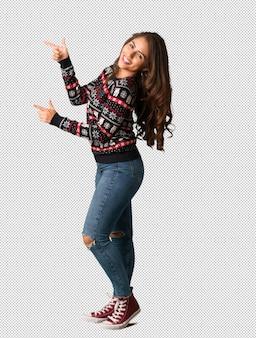 Mujer joven de cuerpo completo con una camiseta navideña apuntando hacia un lado con el dedo