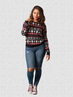 Mujer joven de cuerpo completo con un jersey navideño mostrando el número uno