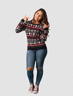 Mujer joven de cuerpo completo vestida con un jersey de navidad sonríe, señalando boca