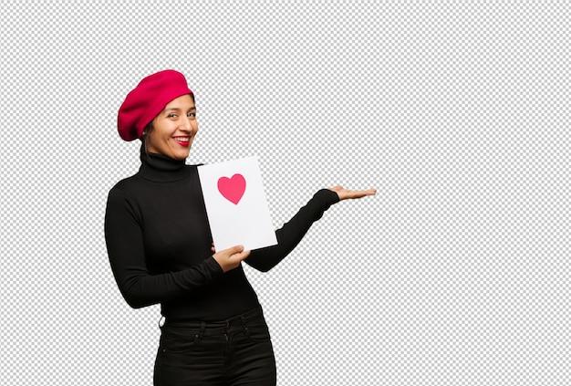 Mujer joven en el día de tarjetas del día de san valentín que lleva a cabo algo con las manos