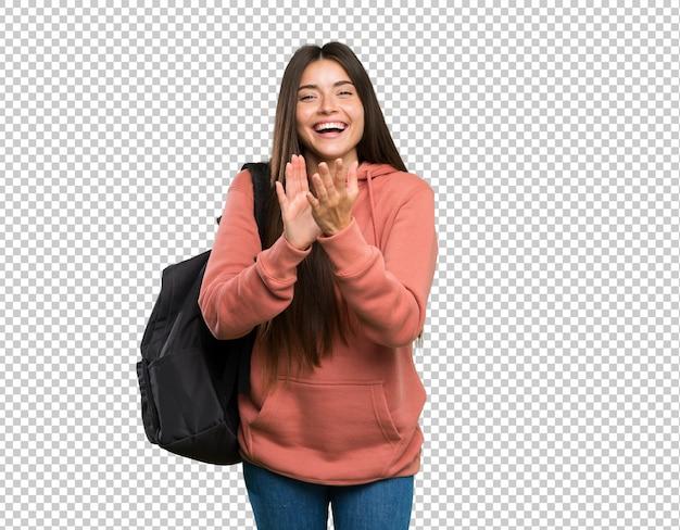 Mujer joven estudiante sosteniendo cuadernos aplaudiendo después de la presentación en una conferencia