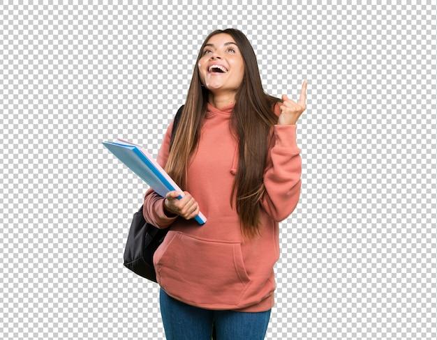 Mujer joven estudiante sosteniendo cuadernos apuntando hacia arriba y sorprendido
