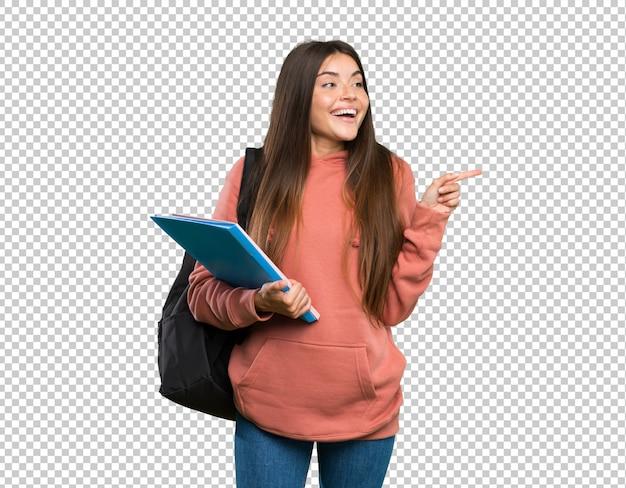 Mujer joven estudiante sosteniendo cuadernos apuntando con el dedo al lado