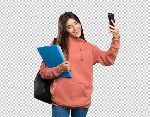 Mujer joven estudiante sosteniendo cuadernos haciendo un selfie