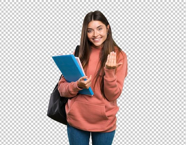 Mujer joven estudiante sosteniendo cuadernos invitando a venir con la mano. feliz de que hayas venido