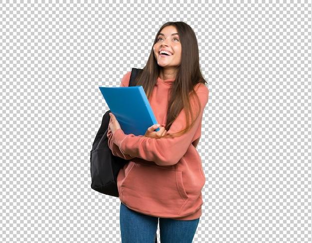 Mujer joven estudiante sosteniendo cuadernos mirando hacia arriba mientras sonríe