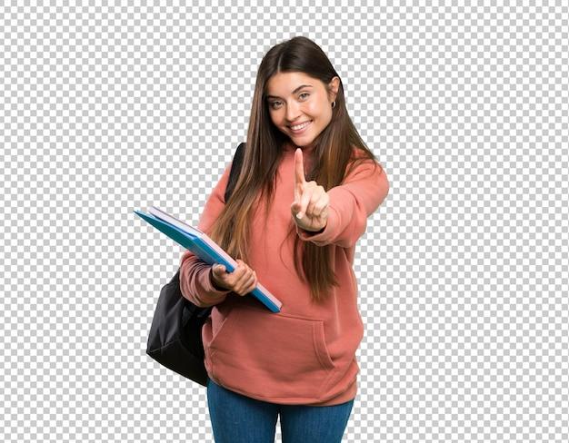 Mujer joven estudiante sosteniendo cuadernos mostrando y levantando un dedo