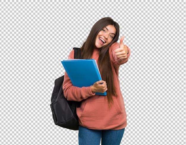 Mujer joven estudiante sosteniendo cuadernos con los pulgares hacia arriba porque algo bueno ha sucedido