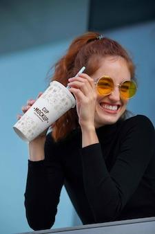 Mujer joven y hermosa bebiendo de maqueta de taza