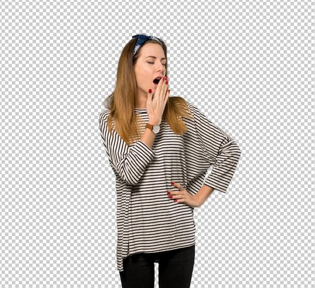 Mujer joven con pañuelo en la cabeza bostezando y cubriendo la boca abierta con la mano