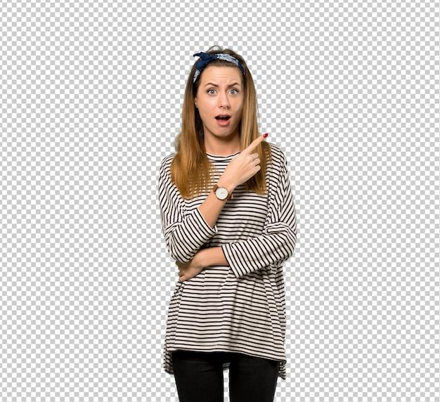 Mujer joven con pañuelo en la cabeza sorprendido y señalando el lado.