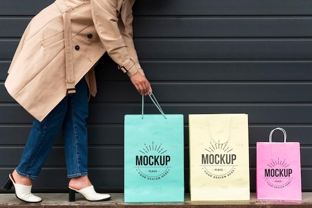 Mujer joven de pie junto a bolsas de la compra.