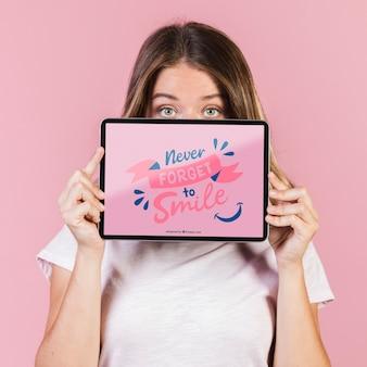 Mujer joven que cubre la cara hasta los ojos con una maqueta de tableta