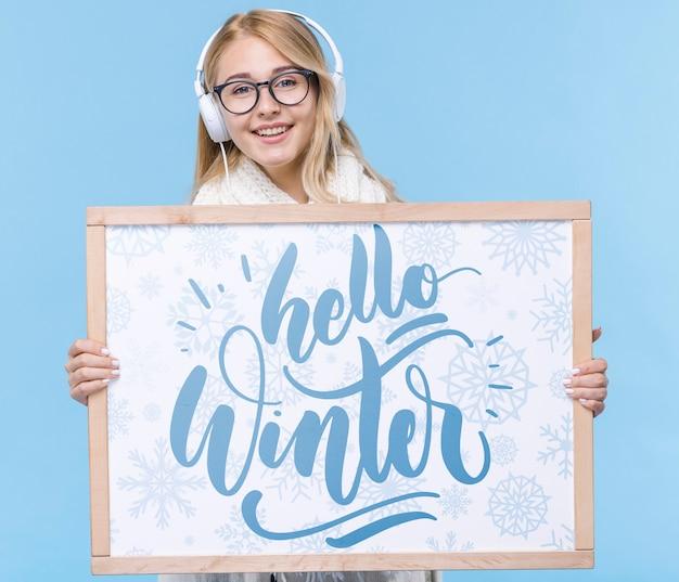 Mujer joven sonriente con cartel de maqueta